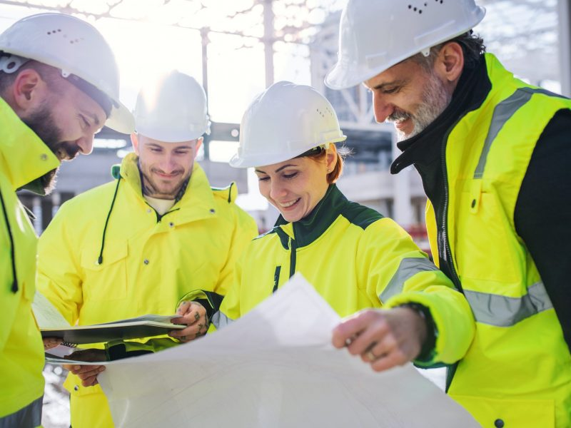 A group of male and female engineers standing on construction site, working.